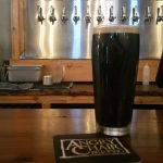 A pint of stout sitting in front of the taps at Angry Chair Brewing in Tampa